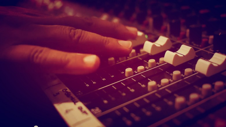 Close up of hands touching faders on a mixing console